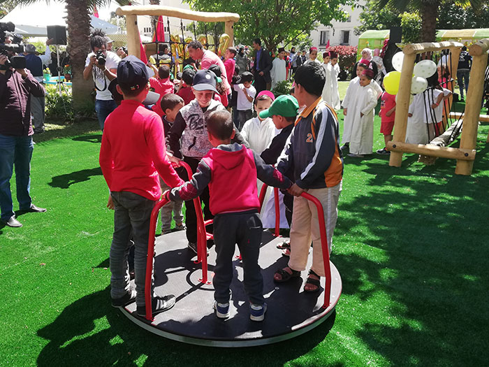 Children playing on the Merry Roundabout in a Moroccan Orphanage Play Area