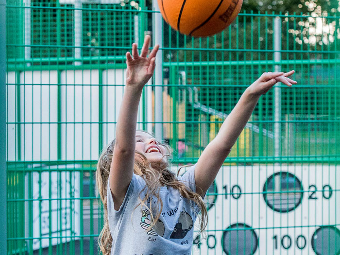 Young girl playing basketball on a multi sports court