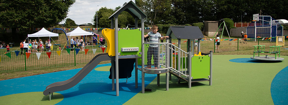 Boy playing on a small multi play unit in green