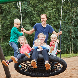 Children and parents swinging on a group basket swing