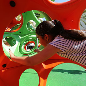 Girl climbing through the PlayCubes climbing frame