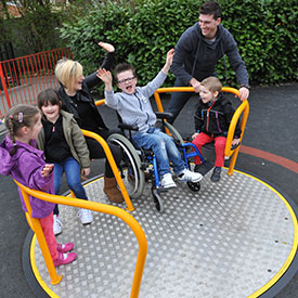 Children and parents enjoying the inclusive wheelchair friendly roundabout Spinmee