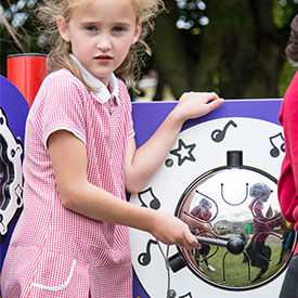 Girl playing with an outdoor musical drum play panel
