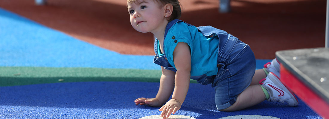 Girl crawling on a coloured playground surface