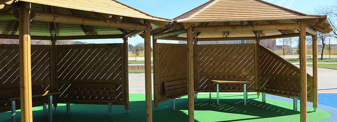 A gathering space in a playground with benches and shelters in timber