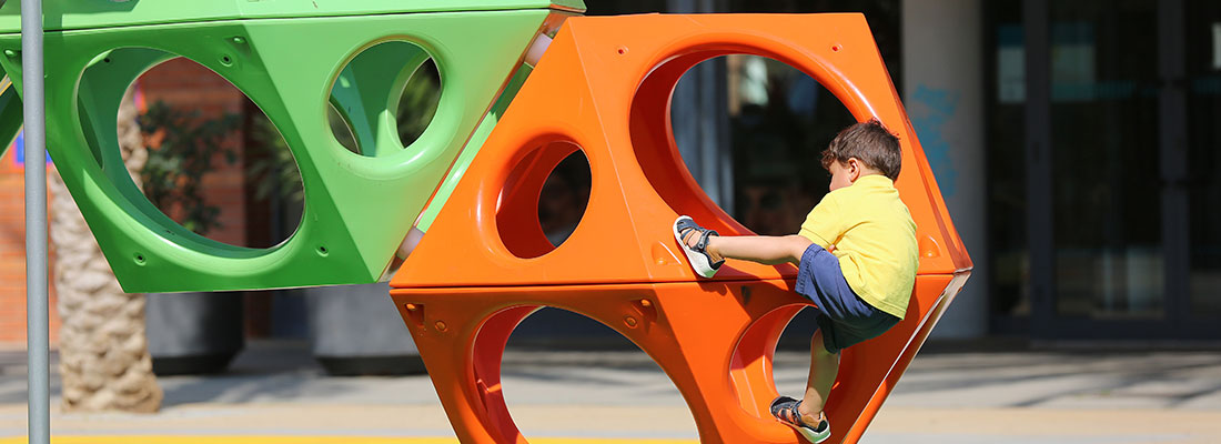 Boy climbing on a cube shaped climbing structure