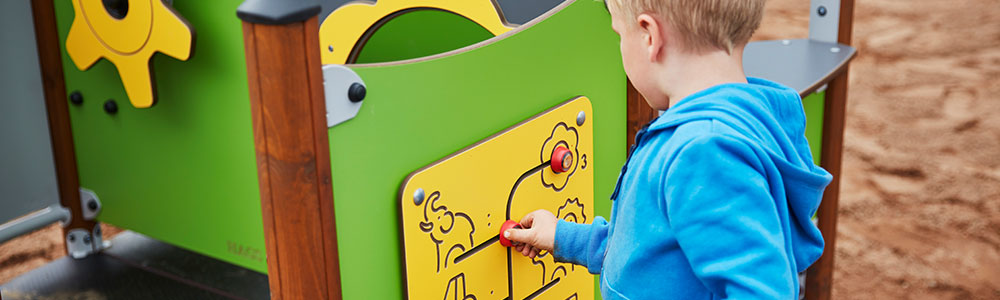 A boy playing on a multi-sensory play panel in a playground