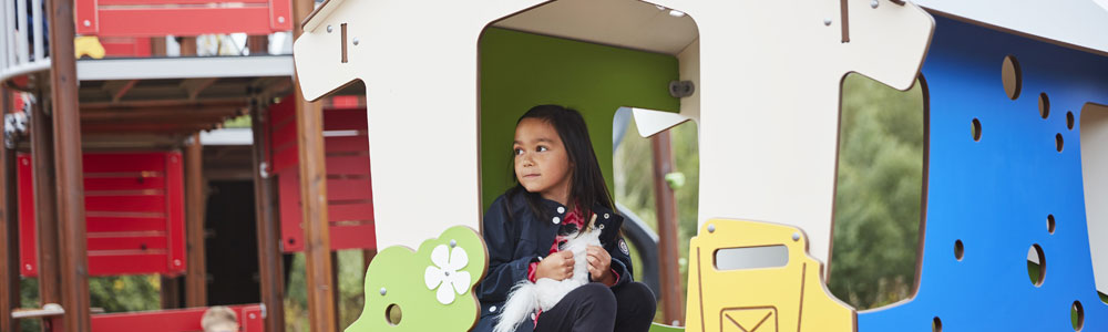 Girl resting in a playground playhouse